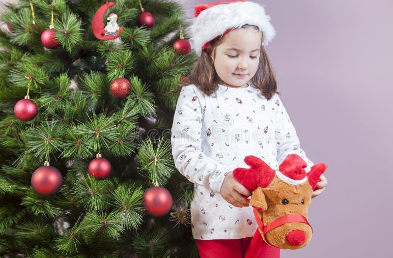 Muchacha del pequeño niño que juega con el juguete del reno del palillo al lado de Christm imágenes de archivo libres de regalías