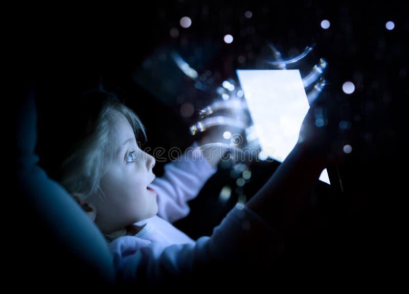Muchacha del pequeño niño que usa tecnología de la tableta en cama por noche en casa hija sorprendida del niño en película de obs imágenes de archivo libres de regalías