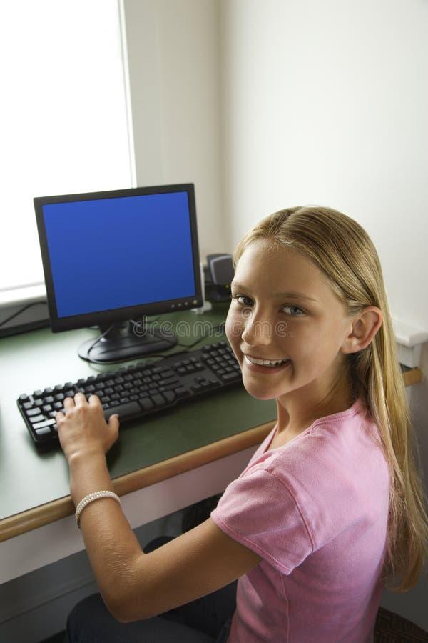Muchacha del Pre-teen en la sonrisa del ordenador. fotos de archivo