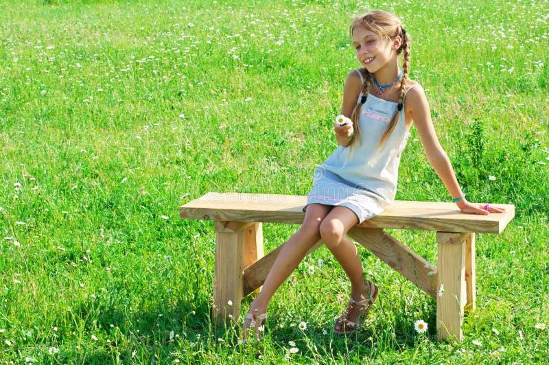 Muchacha del preadolescente en banco en hierba foto de archivo