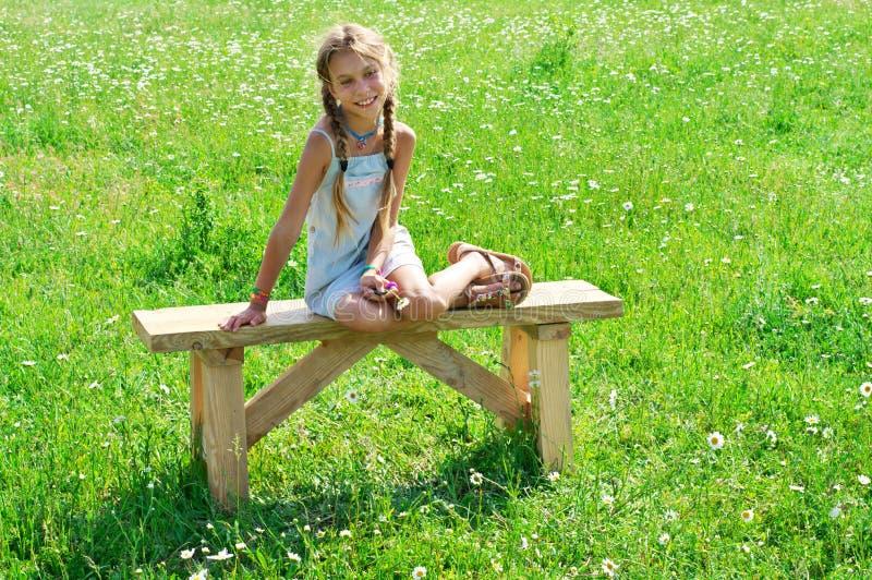 Muchacha del preadolescente en banco en hierba fotografía de archivo