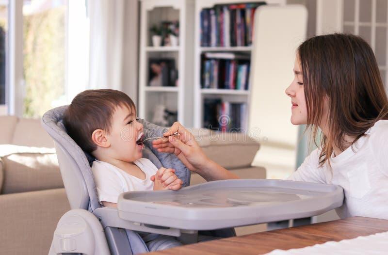 Muchacha del preadolescente que cuida que alimenta a su pequeño hermano que se sienta en silla de alimentación de la altura en ca fotografía de archivo libre de regalías