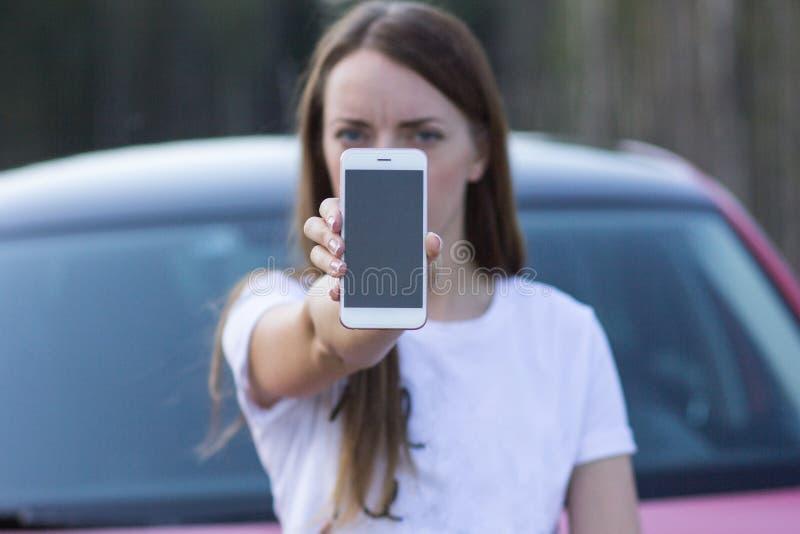 Muchacha del primer que sostiene el smartphone, espacio para el texto imagen de archivo