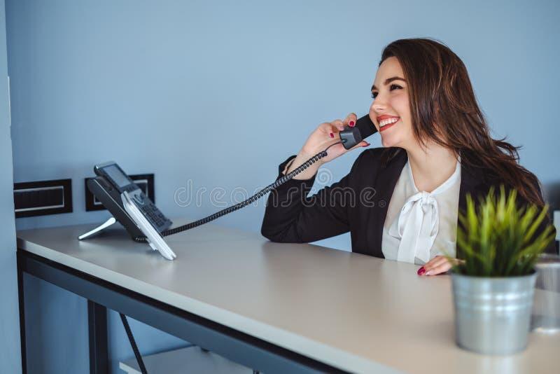 Muchacha del recepcionista que habla en el teléfono y la sonrisa imagenes de archivo