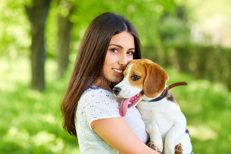 Muchacha del retrato con el beagle del perro en el parque fotos de archivo libres de regalías