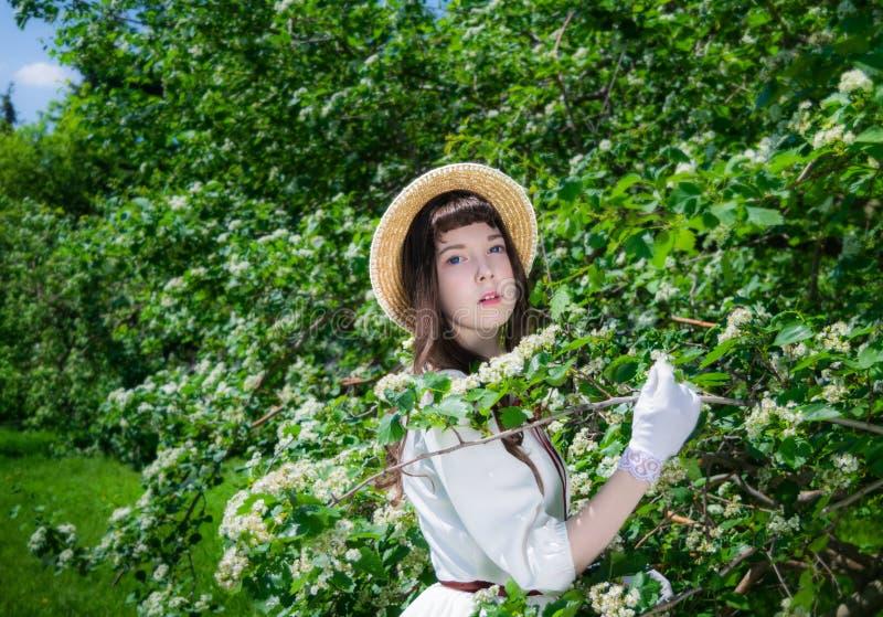 Muchacha del retrato en un sombrero blanco del vestido y de paja cerca foto de archivo libre de regalías