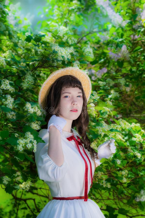 Muchacha del retrato en un sombrero blanco del vestido y de paja cerca de la primavera floreciente del árbol foto de archivo
