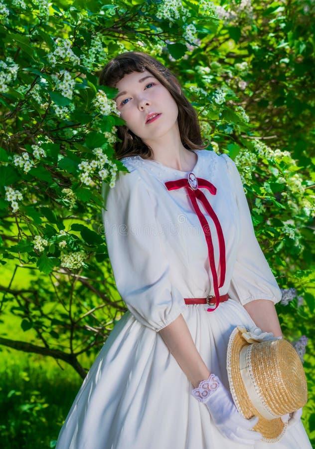 Muchacha del retrato en un sombrero blanco del vestido y de paja cerca de la primavera floreciente del árbol foto de archivo libre de regalías