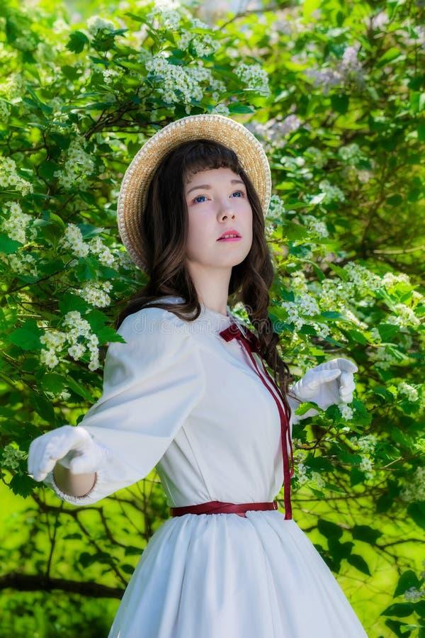 Muchacha del retrato en un sombrero blanco del vestido y de paja cerca de la primavera floreciente del árbol imágenes de archivo libres de regalías