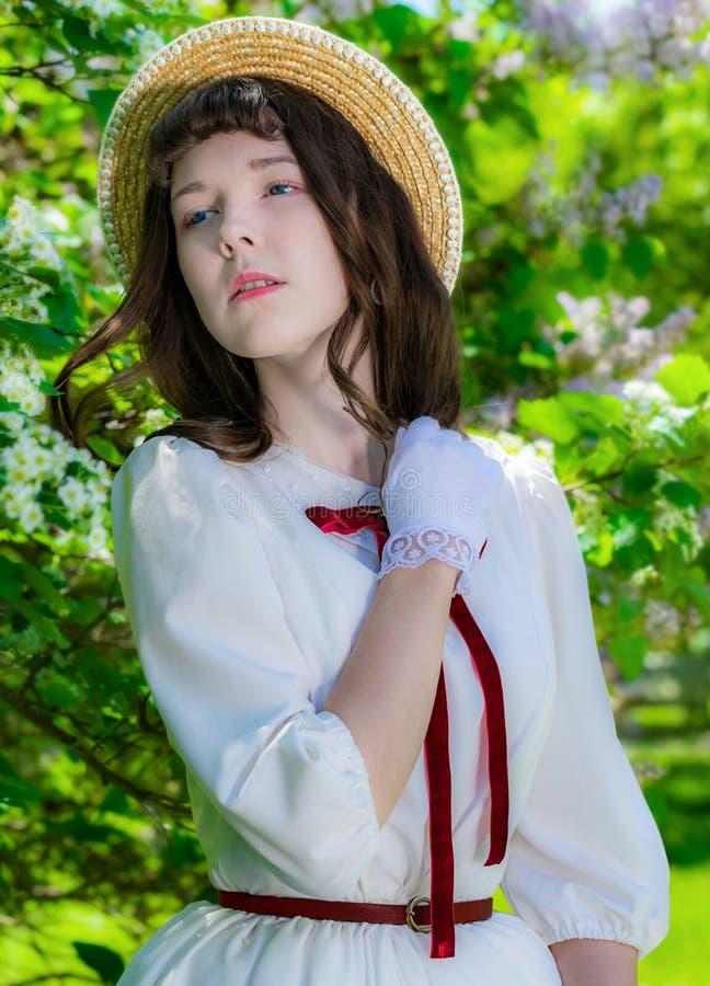 Muchacha del retrato en un vestido blanco cerca del arbusto floreciente del espino en día de primavera imagen de archivo libre de regalías