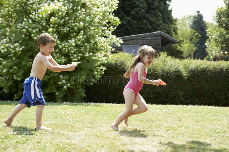 Muchacha del tiroteo del muchacho con la pistola de agua en patio trasero fotografía de archivo