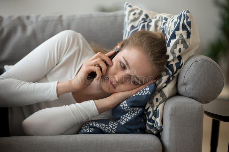 Muchacha del trastorno que miente en el sofá que tiene charla desagradable del teléfono foto de archivo