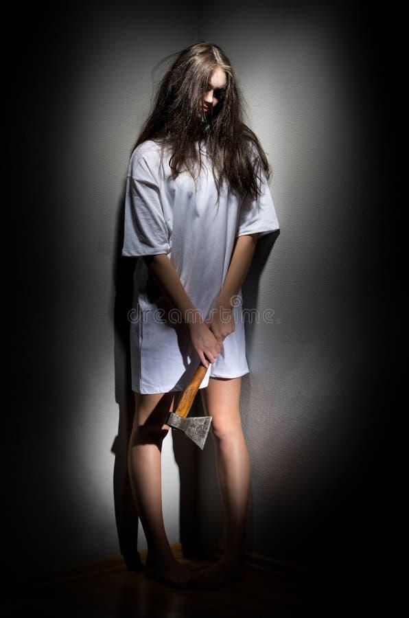 Muchacha del zombi con el hacha imagen de archivo