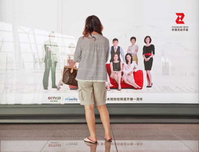 Muchacha delante del anuncio en el aeropuerto de Pekín Capitl Internationl foto de archivo