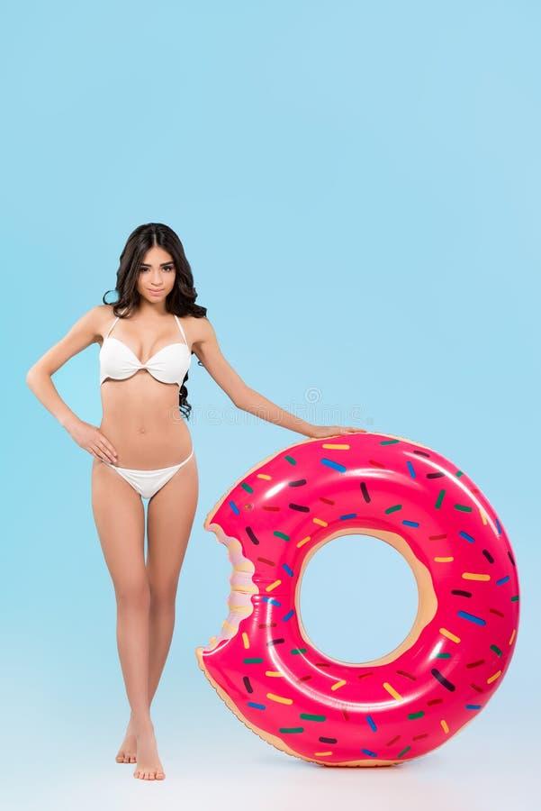 muchacha delgada atractiva que presenta con el anillo inflable del buñuelo, imágenes de archivo libres de regalías
