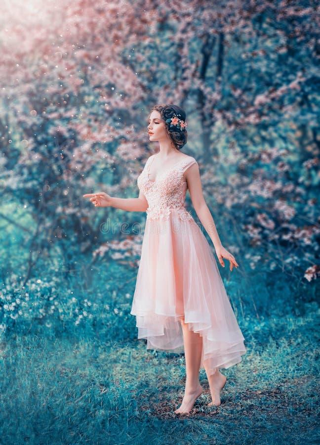 Muchacha delgada bonita con el pelo oscuro trenzado en un vestido elegante delicado del melocot?n, princesa del hada-cuento en un imágenes de archivo libres de regalías