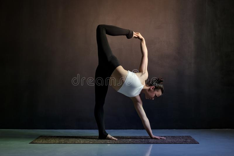 Muchacha delgada caucásica joven de la yoga que hace la variación del shvanasana del mukha del adho imagen de archivo libre de regalías
