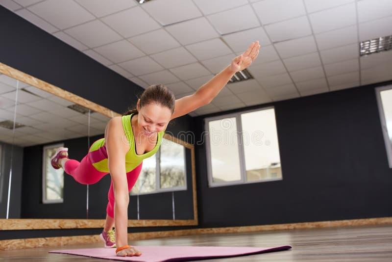 Muchacha delgada del atleta de la mujer joven de la aptitud que hace ejercicio con las piernas en la estera rosada de la yoga foto de archivo libre de regalías