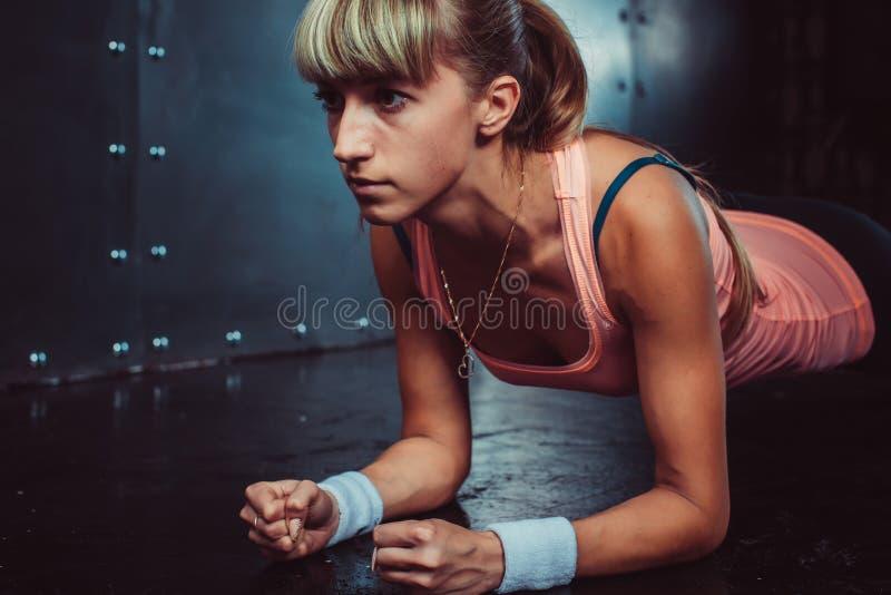 Muchacha delgada del atleta de la mujer joven de la aptitud que hace el tablón imagen de archivo libre de regalías