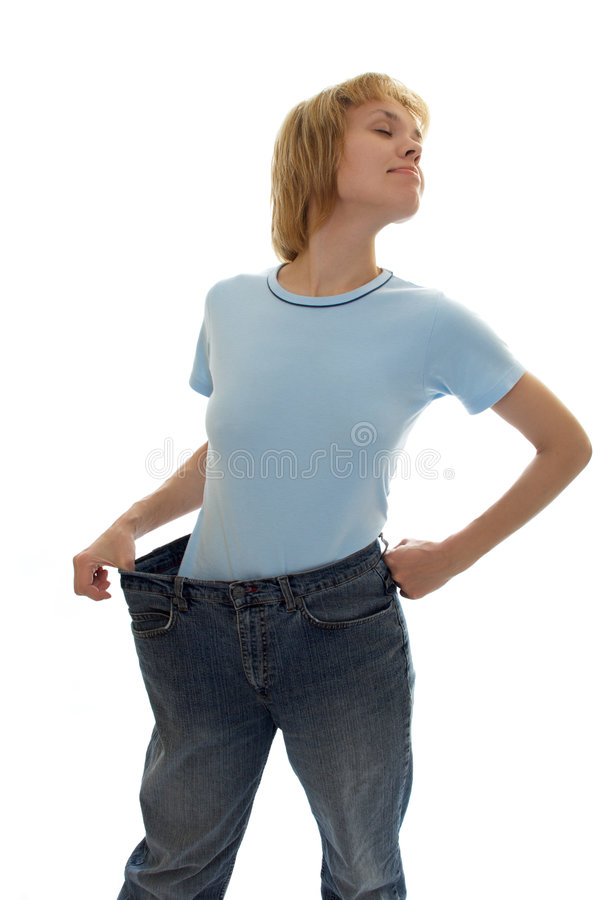 Muchacha delgada en pantalones vaqueros grandes de la talla foto de archivo