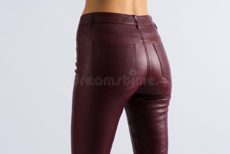 Muchacha delgada hermosa del botín Pantalones flacos de cuero de Borgoña con los bolsillos Cierre encima de la visión encendido y fotos de archivo