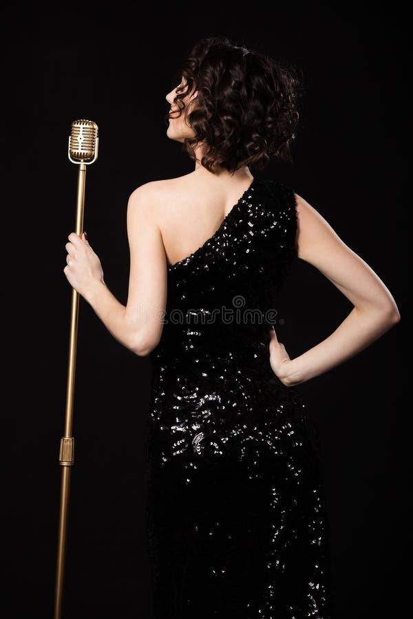 Muchacha delgada hermosa del cantante que sostiene el micrófono de oro del vintage imagenes de archivo