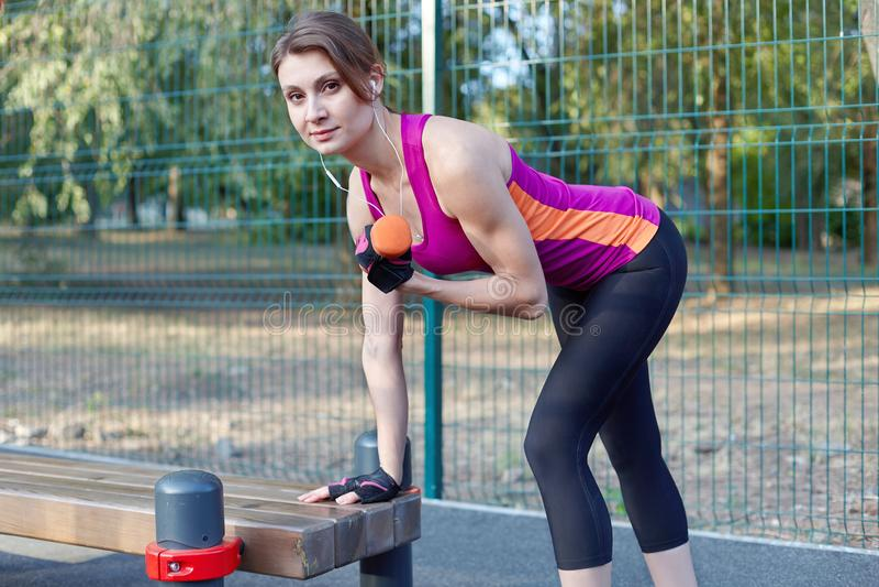 Muchacha delgada hermosa que sonríe, en trenes brillantes de la ropa de deportes con la pesa de gimnasia para el bíceps en el spo fotos de archivo
