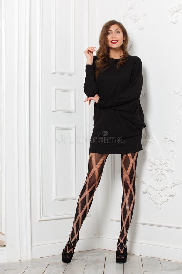 Muchacha delgada hermosa vestida en un vestido corto negro elegante y actitudes de moda de las medias contra una pared blanca en  foto de archivo libre de regalías