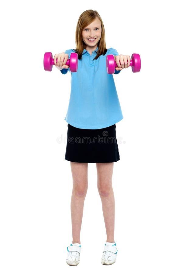 Muchacha delgada pulso una actitud con pesas de gimnasia imagen de archivo