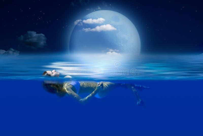 Muchacha delgada que miente en el agua en el claro de luna imagen de archivo