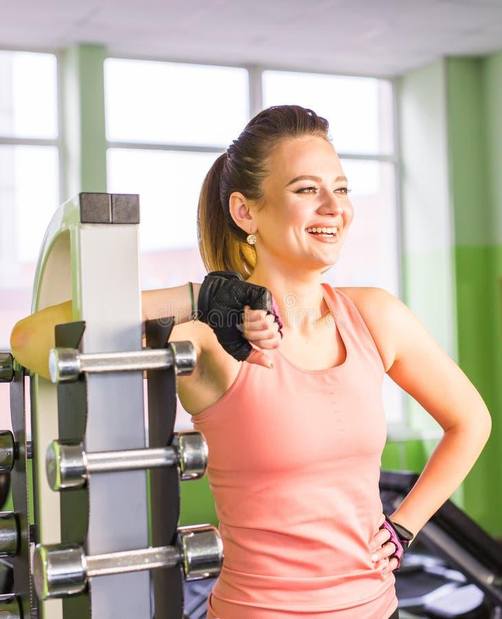 Muchacha deportiva apta del adulto joven que presenta cerca de estante con pesa de gimnasia del metal en espacio del sitio del gi imagenes de archivo