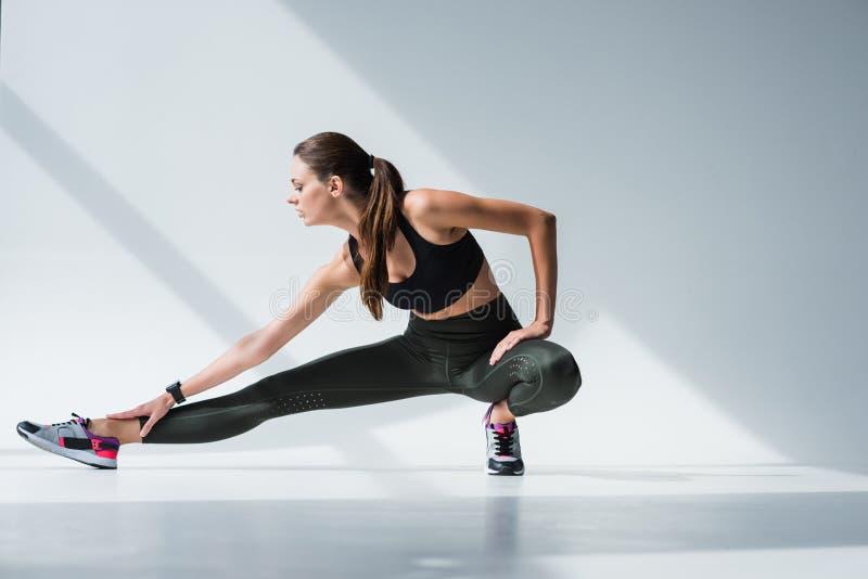 muchacha deportiva atractiva que estira las piernas antes de entrenamiento foto de archivo