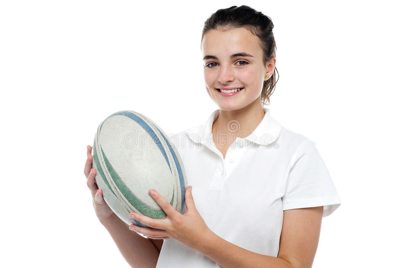 Muchacha deportiva atractiva que presenta con la bola de rugbi fotos de archivo libres de regalías