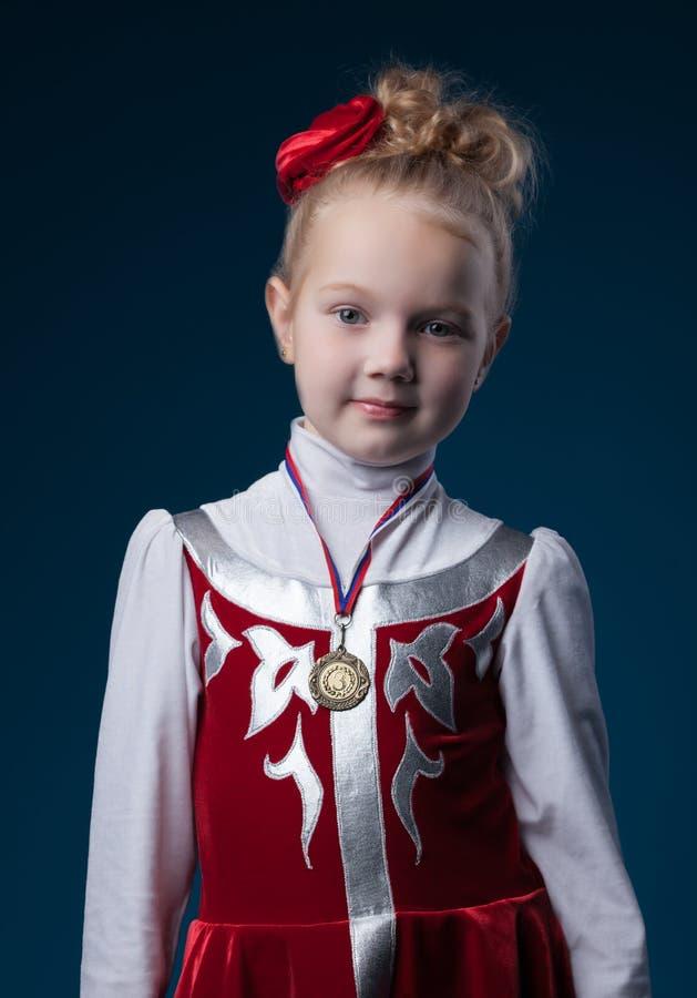 Muchacha deportiva bastante pequeña que presenta con la medalla fotografía de archivo