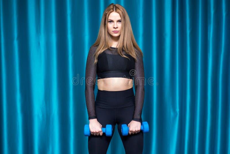 Muchacha deportiva bonita que hace ejercicios con pesas de gimnasia fotos de archivo