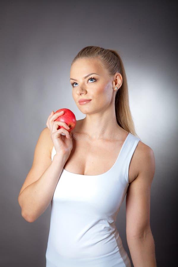 Muchacha deportiva con una manzana roja imagenes de archivo