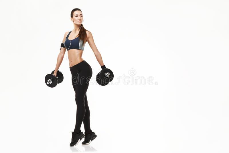 Muchacha deportiva de la aptitud joven en auriculares que entrena llevando a cabo pesas de gimnasia sobre el fondo blanco imagen de archivo libre de regalías