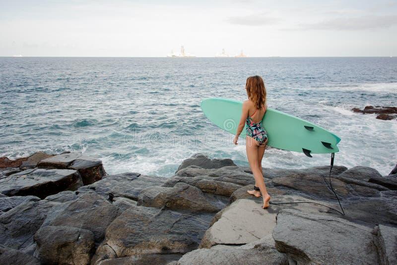 Muchacha deportiva de la vista posterior en el traje de baño coloreado multi que camina con la resaca en las rocas en la playa fotos de archivo libres de regalías