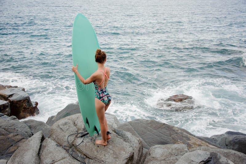 Muchacha deportiva de la vista posterior en la situación coloreada multi del traje de baño con la resaca en la playa de la roca imagen de archivo libre de regalías