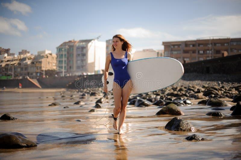 Muchacha deportiva en el traje de baño azul que camina con la tabla hawaiana blanca foto de archivo