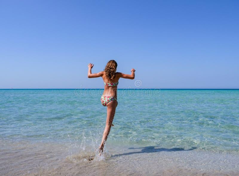 Muchacha deportiva hermosa en un bikini colorido que salta en el agua de la turquesa de una playa hermosa imagenes de archivo