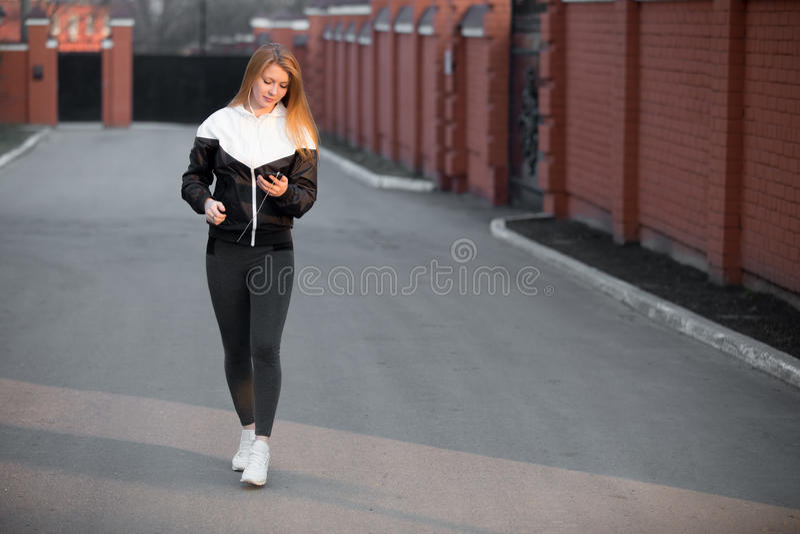 Muchacha deportiva hermosa que usa el dispositivo que camina en la calle imagen de archivo