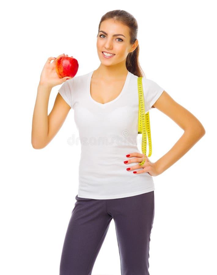 Muchacha deportiva joven con la manzana y la cinta de la medida imagenes de archivo