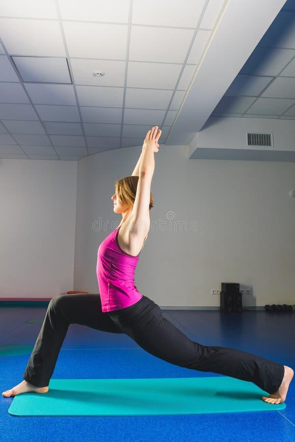 Muchacha deportiva joven que hace ejercicios gimnásticos en clase de la aptitud imagen de archivo