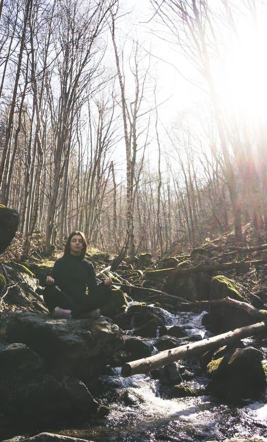 Muchacha deportiva joven que hace el loto de la actitud de la yoga que se sienta en una roca en un río que medita en el bosque co imágenes de archivo libres de regalías