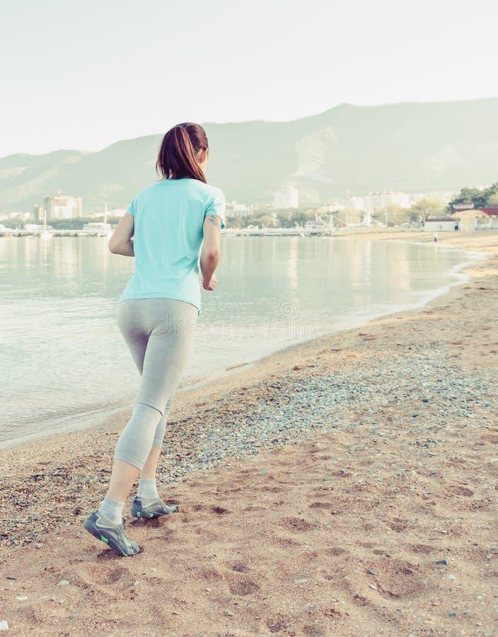Muchacha deportiva que corre en la playa de la arena foto de archivo libre de regalías
