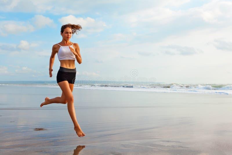 Muchacha deportiva que corre por la playa a lo largo de la resaca del mar imagenes de archivo
