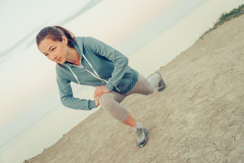 Muchacha deportiva que estira sus piernas fotos de archivo