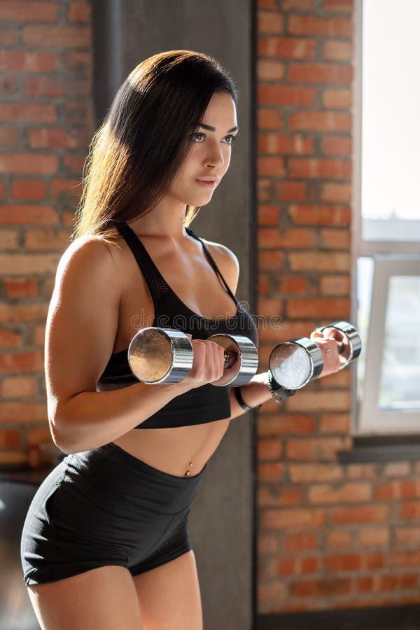 Muchacha deportiva que hace ejercicio con pesas de gimnasia fotos de archivo
