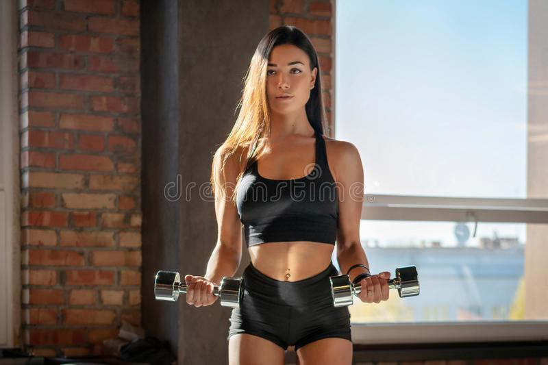 Muchacha deportiva que hace ejercicio con pesas de gimnasia foto de archivo libre de regalías